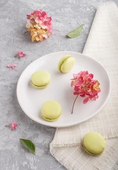 Zieleni macarons lub macaroons zasychają na białym ceramicznym talerzu na szarym betonie, boczny widok.