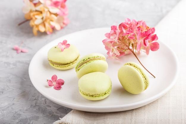 Zieleni macarons lub macaroons zasychają na białym ceramicznym talerzu na szarym betonie ukazują się bocznego widok, selekcyjna ostrość.