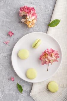 Zieleni macarons lub macaroons zasychają na białym ceramicznym talerzu na szarym betonie ukazują się odgórnego widok.