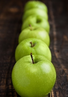 Zieleni organicznie zdrowi jabłka na drewnianej desce