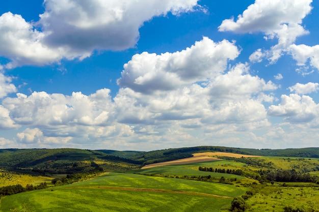 Zieleni pola na wzgórzach pod niebieskim niebem z bufiastymi chmurami