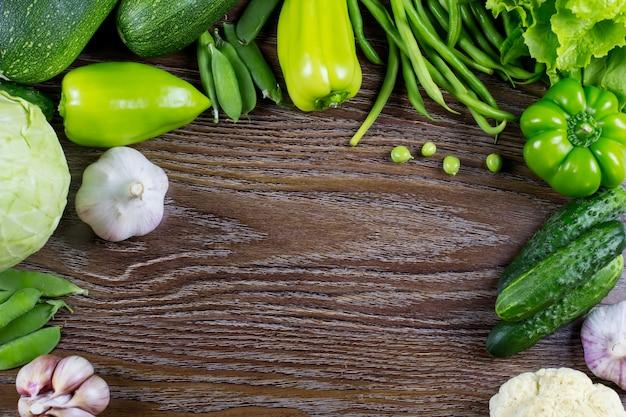 Zieleni warzywa żniwo, surowa zdrowa żywność organiczna na drewnianym tle