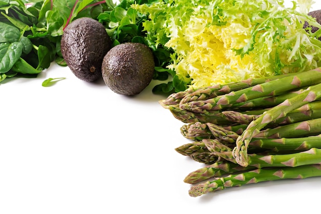 Zieleni ziele, asparagus i czarny avocado na białym tle. widok z góry.