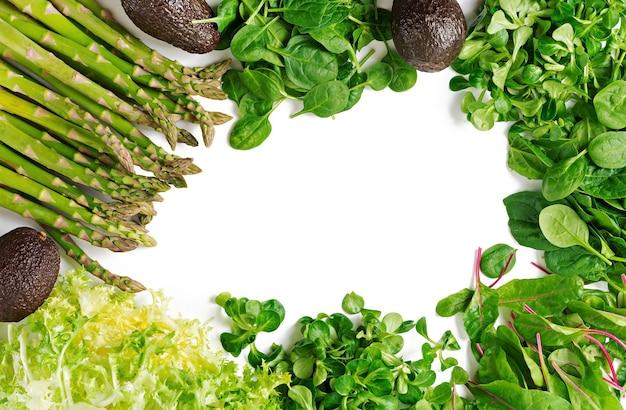 Zieleni ziele, asparagus i czarny avocado na białym tle.