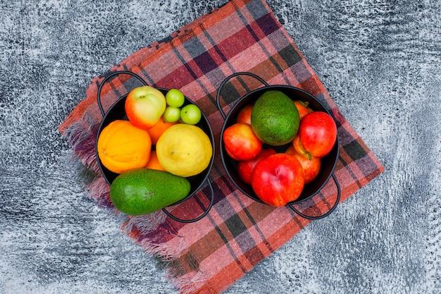 Zieleniaki, brzoskwinie, awokado i owoce cytrusowe w dwóch czarnych rondlach na tkaninie piknikowej i grunge. leżał płasko.