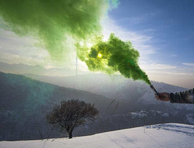Zielona bomba dymna w ręku