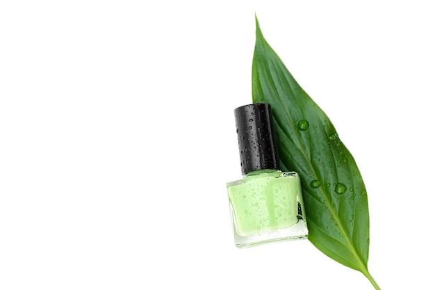 Zielona butelka lakieru do paznokci na białej powierzchni.