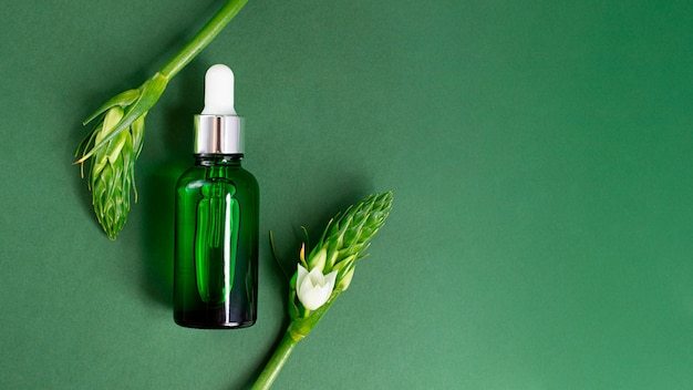 Zielona butelka na kosmetyki na ciemnozielonym tlemakieta kosmetyczna z kopią przestrzeńduży baner