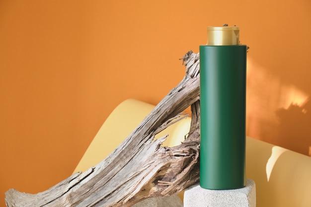 Zielona butelka na szampon lub balsam do włosów na betonowym podium na tle drewnianego drewna dryfującego, brązowe tło, światło słoneczne z okna, piękne cienie