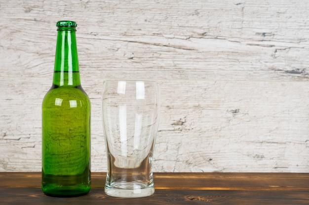 Zielona butelka piwa z pustą szklanką na stole do pubu