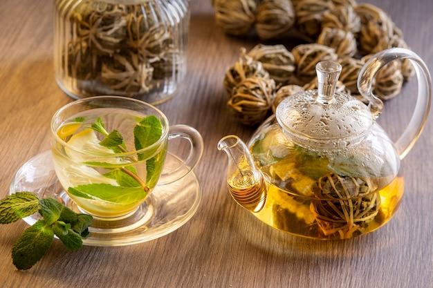 Zielona chińska herbata z cytryną i miętą na drewnianym stole.