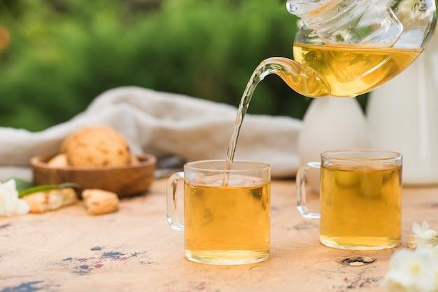 Zielona chińska herbata z jaśminem przelewa się z czajnika do kubka
