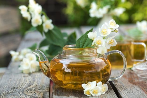 Zielona chińska herbata z jaśminem w czajniczku na drewnianym blacie na tle jaśminowej k...