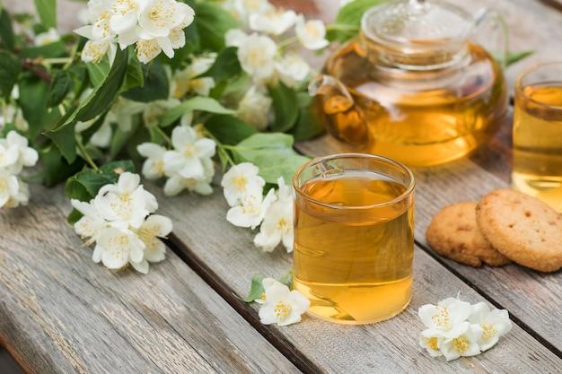 Zielona chińska herbata z jaśminem w kubkach i czajniczek na drewnianym blacie z bukietem jaśminu...