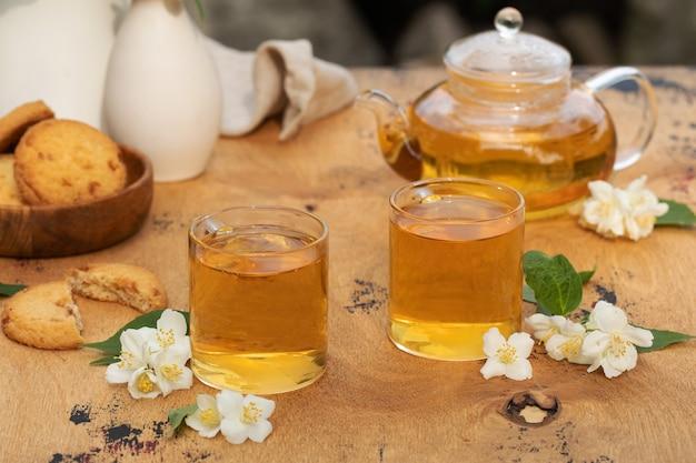 Zielona chińska herbata z jaśminem w kubkach i czajniczku na drewnianym blacie z kwiatami jaśminu