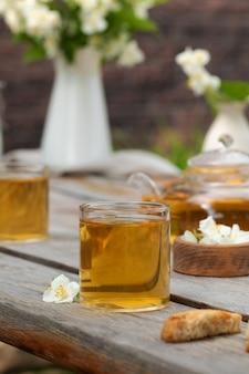 Zielona chińska herbata z jaśminem w kubku z kwiatami jaśminu