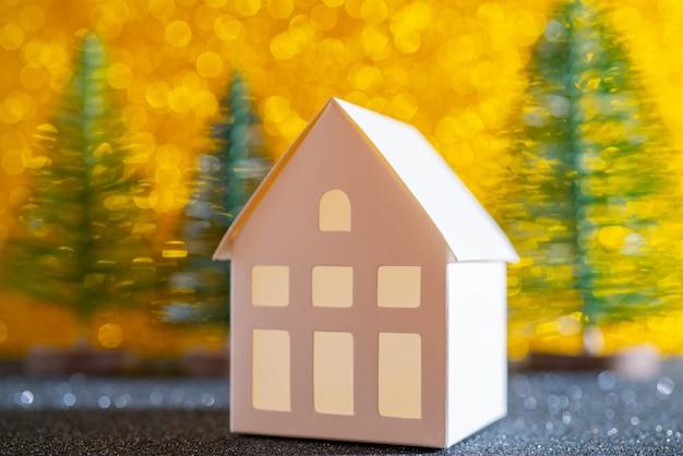 Zielona choinka na błyszczącym tle. piękny efekt bokeh. mały biały domek.