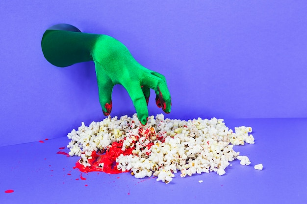 Zielona dłoń dotarstająca popcornem