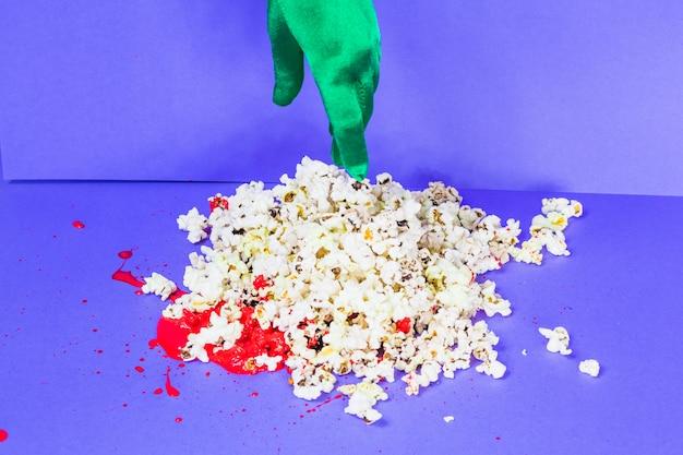 Zielona dłoń dotykając popcornu