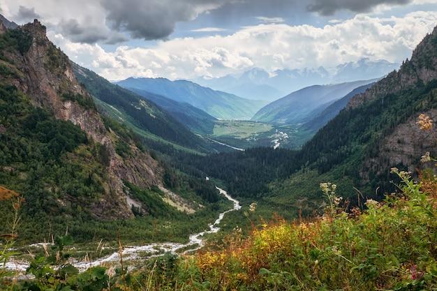 Zielona dolina w georgian svaneti górach z rzeką pod chmurami