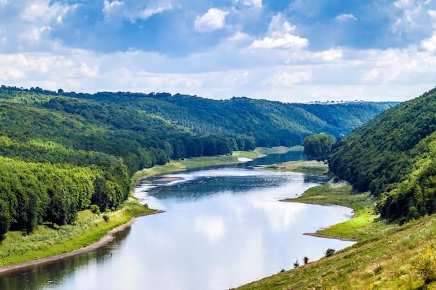Zielona dolina w lecie z lasami na wzgórzach i wielką rzeką poniżej
