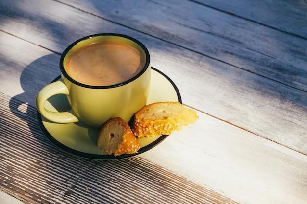 Zielona filiżanka kawy z ciasta domowej roboty na drewnianym stole w godzinach porannych.