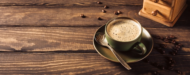 Zielona filiżanka kawy z młynek do kawy