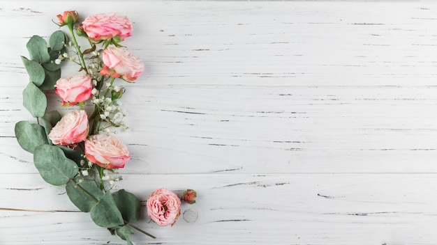 Zielona gałązka; różowe róże i biała łyszczec na białym drewnianym tle z teksturą
