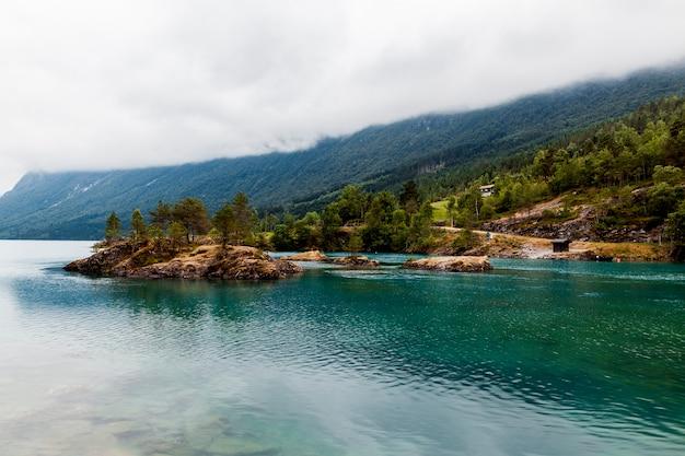 Zielona góra nad błękitnym idyllicznym jeziorem