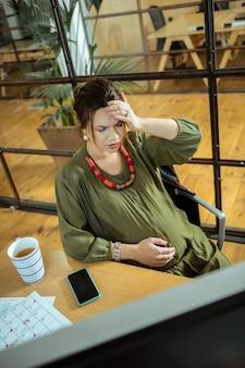 Zielona herbata. ciemnowłosa młoda kobieta w ciąży pijąca zieloną herbatę z bólem głowy
