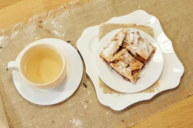 Zielona herbata i ciasto na talerzu. jedzenie jest gotowe do spożycia. ciasto francuskie