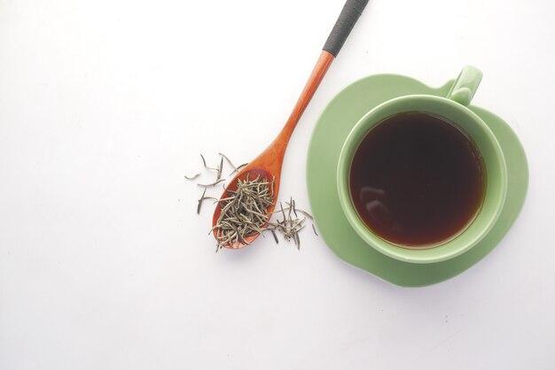 Zielona herbata i suchy liść ziołowy na łyżce na białej powierzchni