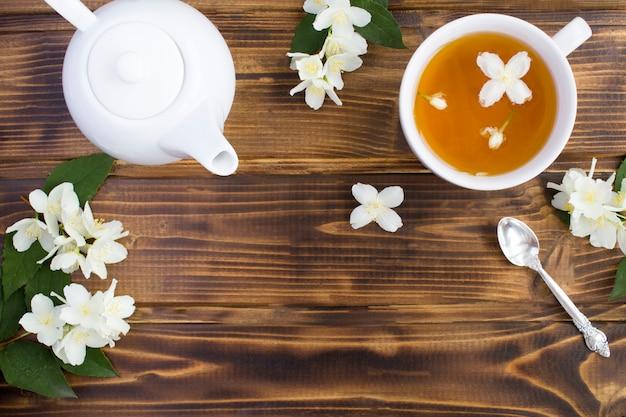 Zielona herbata jaśminowa w białej filiżance, imbryk i kwiaty na brązowej powierzchni drewnianej, widok z góry, miejsce na kopię