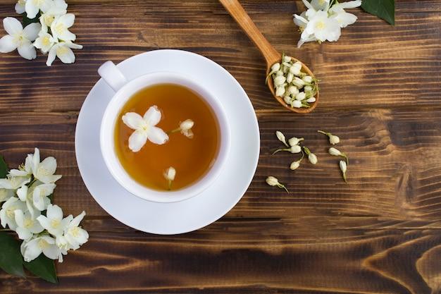 Zielona herbata jaśminowa w białej filiżance na brązowej powierzchni drewnianej, widok z góry, miejsce na kopię