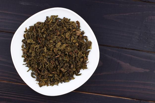 Zielona herbata jest suszona na talerzu, aby uzyskać miejsce na tekst