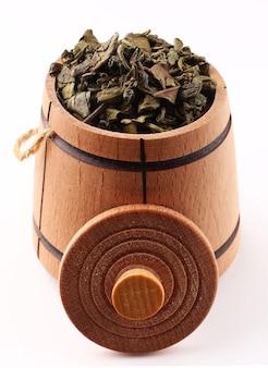Zielona herbata jest suszona w beczce na białej powierzchni