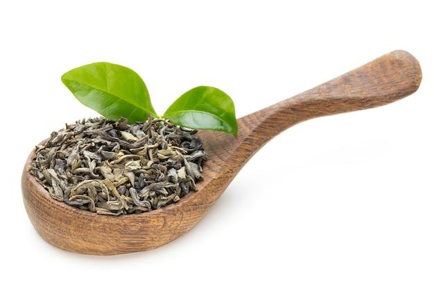 Zielona herbata liść łyżka na białym tle.