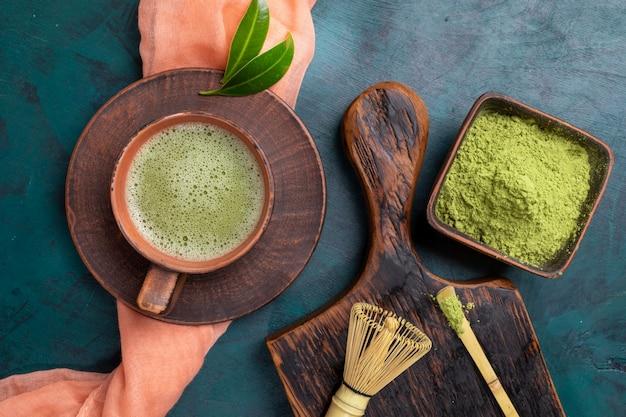 Zielona herbata matcha i proszek na szmaragdowym tle. widok z góry.
