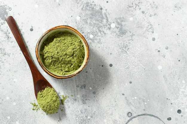 Zielona herbata matcha w proszku z łyżeczką.