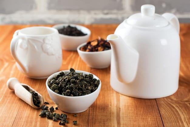 Zielona herbata oolong w białej ceramicznej misce na drewnianym stole.
