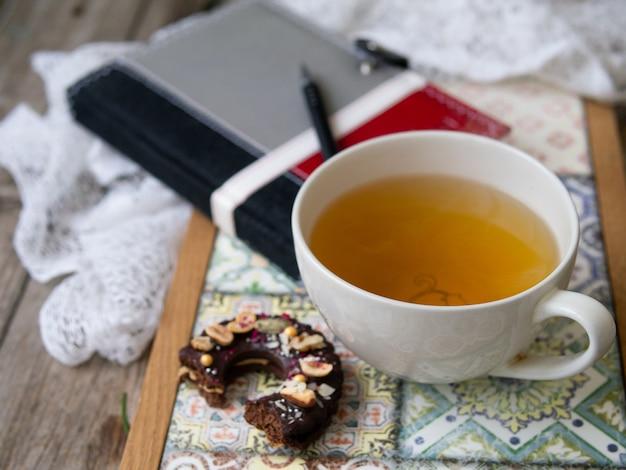 Zielona herbata w dużym białym kubku z czekoladowym ciasteczkiem na kolorowej tacy na drewnianym tle. obrabiany przedmiot z notatnikiem i długopisem. planowanie. śniadanie. ścieśniać.