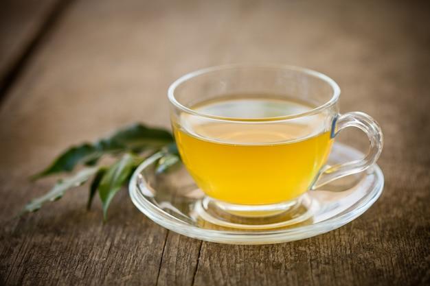 Zielona herbata w szklanej filiżance i kwiaty na drewnianym stole
