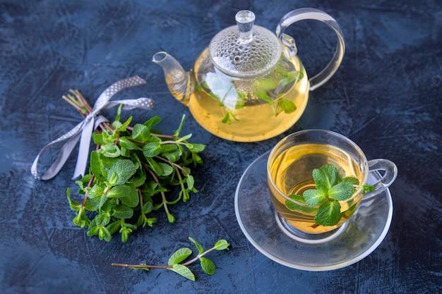 Zielona herbata w szklankach i liście mięty na ciemnym tle stołu
