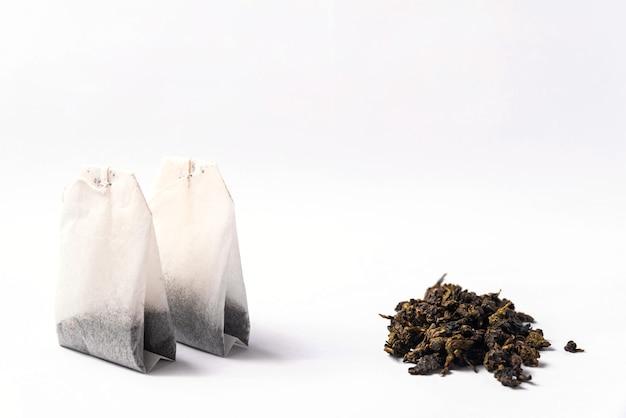 Zielona herbata w torebkach i sypka zielona herbata na białym tle