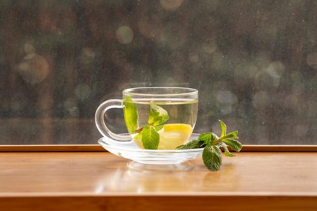 Zielona herbata z cytryną i miętą w przezroczystej szklanej filiżance