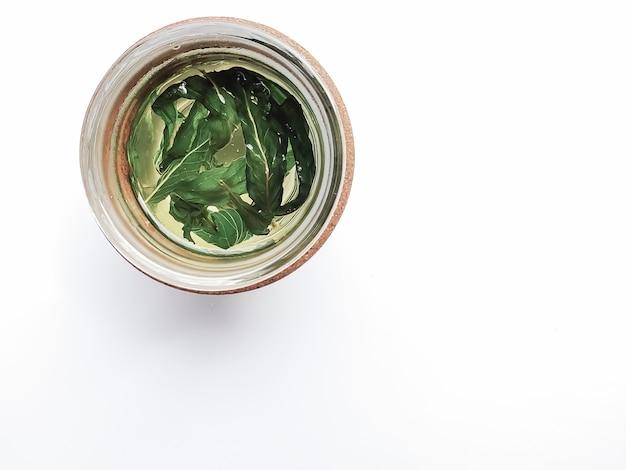 Zielona herbata z dużymi listkami mięty w szklanym kubku