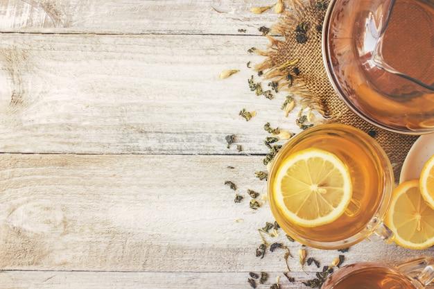 Zielona herbata z jaśminem i czarnym z przezroczystą cytryną w małej filiżance na jasnym tle. ekspres do herbaty. selektywna ostrość.