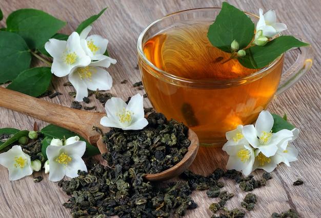Zielona herbata z jaśminem. wytrzyj liście zielonej herbaty z kwiatami jaśminu w drewnianej łyżce i filiżance herbaty na drewnianym stole