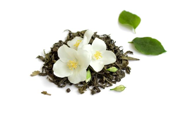 Zielona herbata z kwiatami jaśminu na białym tle z bliska widok z góry