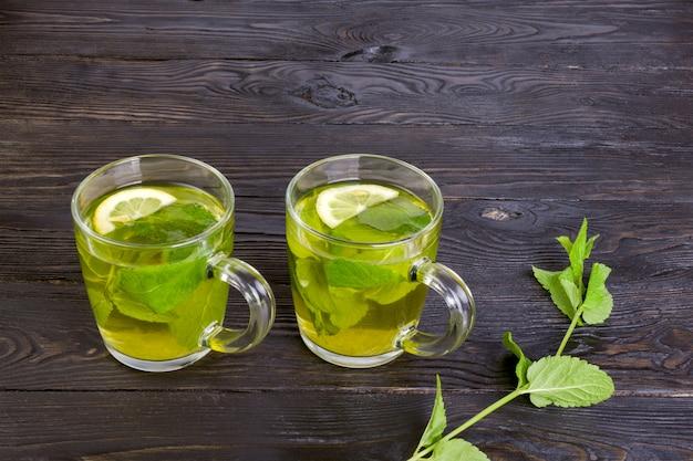 Zielona herbata z miętą i cytryną w dwóch przezroczystych szklanych filiżankach na ciemnym drewnianym stole.